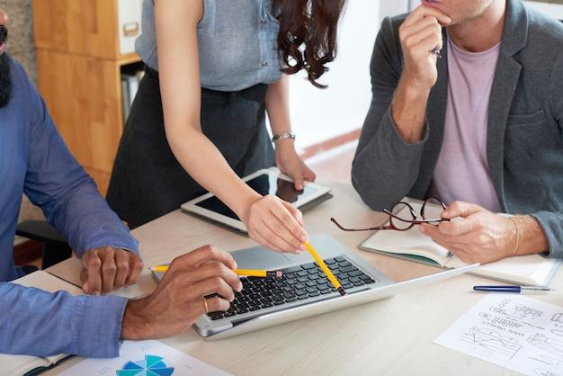 Equipo de negocios haciendo presentación en computadora portátil
