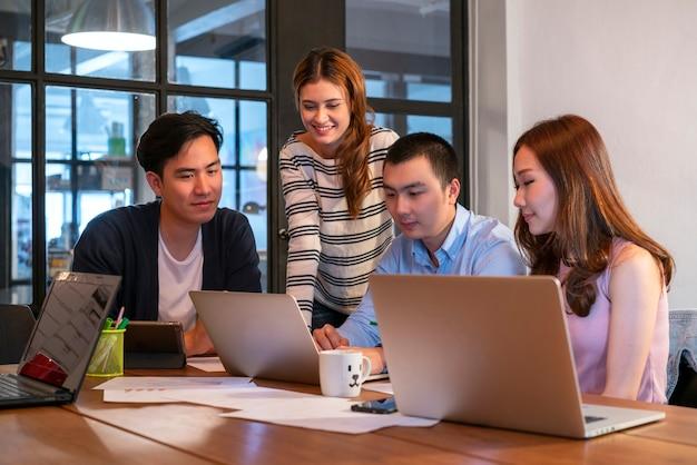 Equipo de negocios de inicio joven asiático en uniforme casual discutiendo y trabajando juntos en la oficina de espacio de trabajo conjunto moderno.