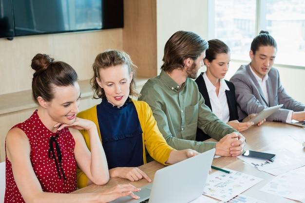Equipo de negocios interactuando entre sí en la sala de conferencias