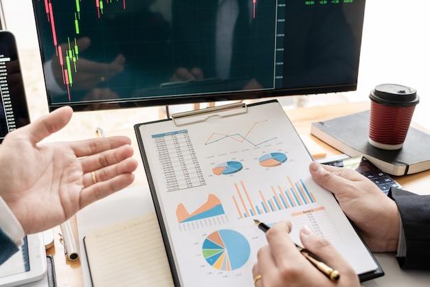 Equipo de negocios inversión emprendedor comercio discutiendo y analizando datos de las tablas y gráficos del mercado de valores negociación y presupuesto de investigación