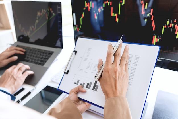 Equipo de negocios inversión emprendedor comercio discutir y analizar datos de los gráficos del mercado de valores