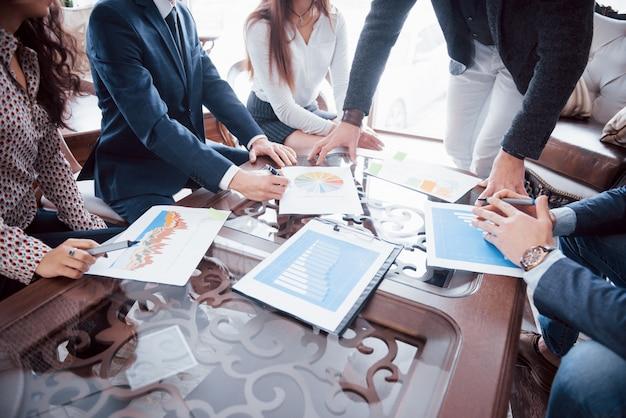 Equipo de negocios lluvia de ideas. plan de marketing de investigación. papeleo sobre la mesa, computadora portátil y teléfono móvil