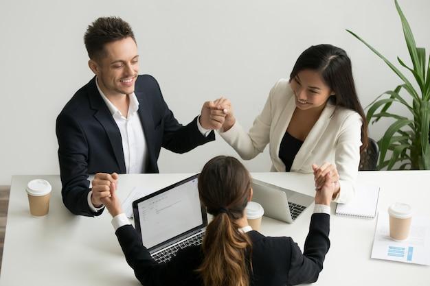 Equipo de negocios meditando juntos tomados de la mano