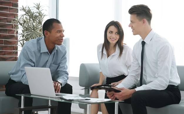 Equipo de negocios mirando portátil mientras está sentado en su escritorio .foto con espacio de copia