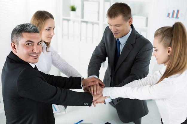 Equipo de negocios mostrando unidad poniendo sus manos juntas una encima de la otra. concepto de trabajo en equipo.