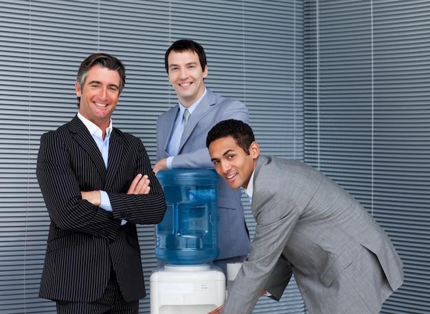 Equipo de negocios multiétnica en enfriador de agua