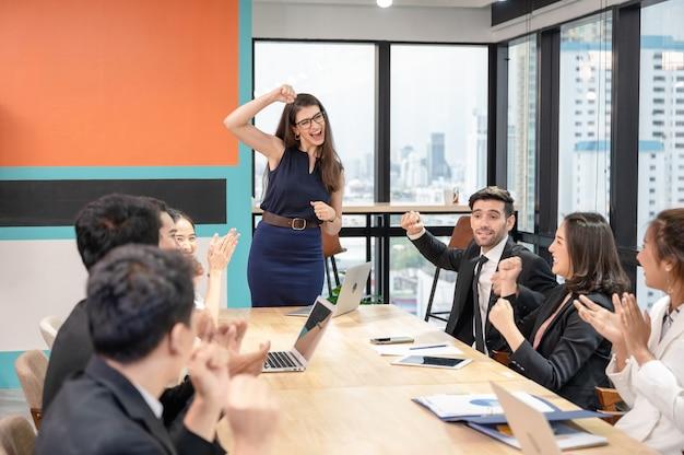 Equipo de negocios multiétnico animando y aplaudiendo el éxito de la empresa en la oficina moderna