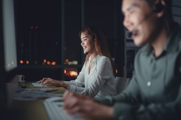 Equipo de negocios de operador de soporte al cliente con auriculares trabajando hasta tarde en la oficina.