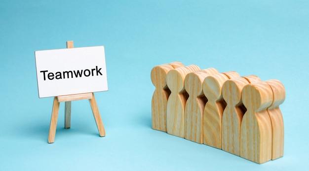 Equipo de negocios está parado cerca del lienzo con la palabra trabajo en equipo. concepto de trabajo en equipo