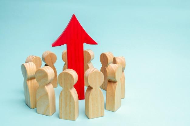 Un equipo de negocios está de pie en un círculo y la flecha está entre los empleados.