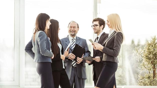 Equipo de negocios profesional con documentos en el centro de la espaciosa oficina.