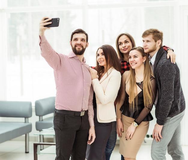 Equipo de negocios profesional haciendo selfie mientras está de pie cerca de la ventana en la oficina moderna