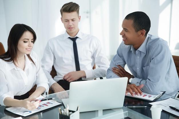 Equipo de negocios profesional que trabaja con documentos financieros sentado en un escritorio