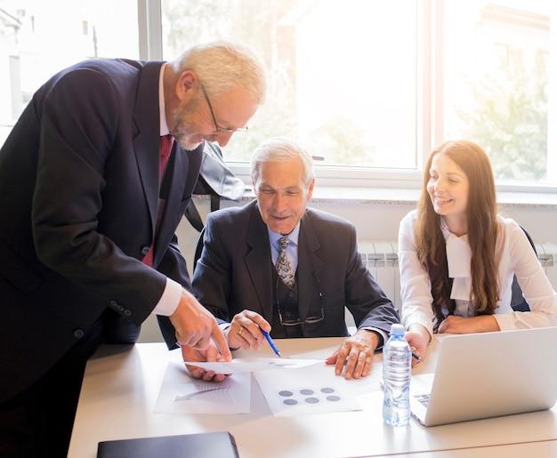 Equipo de negocios que analiza tablas y gráficos de ingresos con una computadora portátil moderna