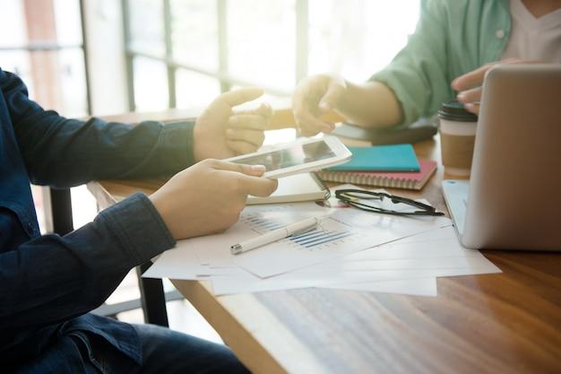 Equipo de negocios que informa la estrategia de marketing con la computadora portátil en casa oficina.
