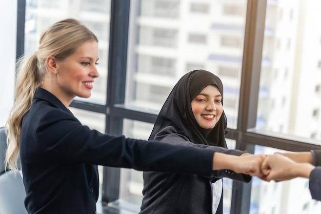 Equipo de negocios que muestra la unidad con sus manos juntas. concepto de unidad y trabajo en equipo.