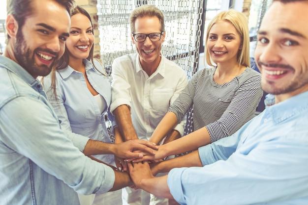 Equipo de negocios en ropa casual está sosteniendo las manos juntas.