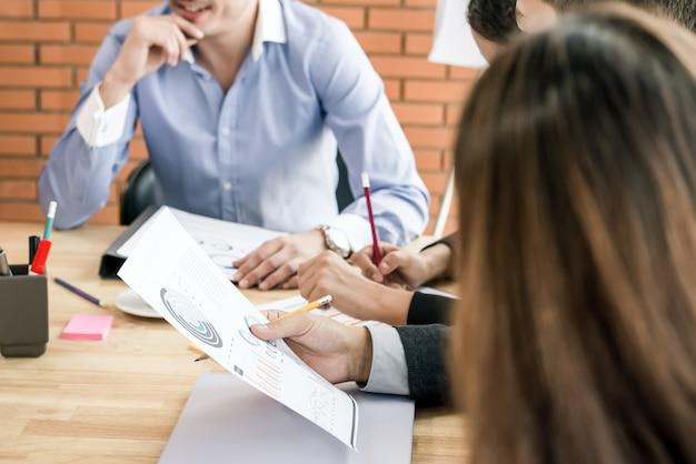 Equipo de negocios en la sala de reuniones discutiendo el documento de datos estadísticos en la mesa
