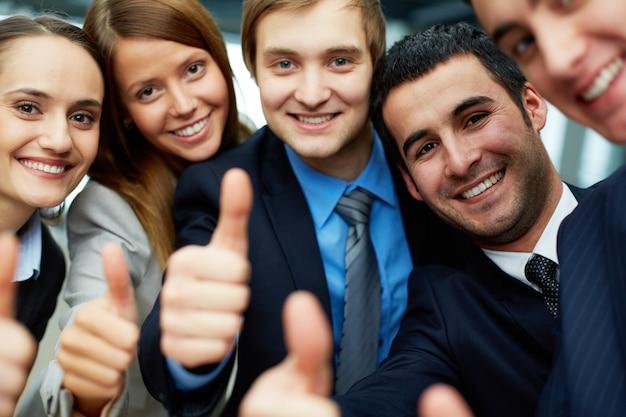 Equipo de negocios sonriente con pulgares levantados
