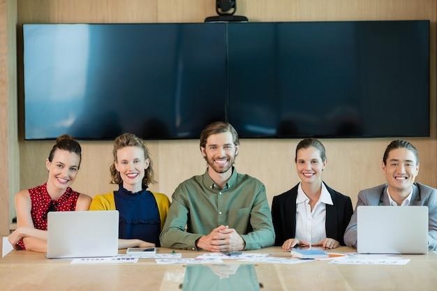 Equipo de negocios sonriente sentado en la sala de conferencias