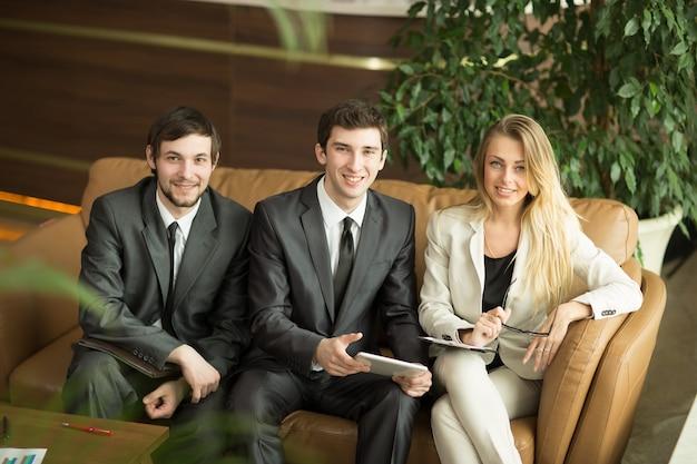 Equipo de negocios con tableta y documentos en un descanso de trabajo, sentado en el sofá en el vestíbulo de la oficina