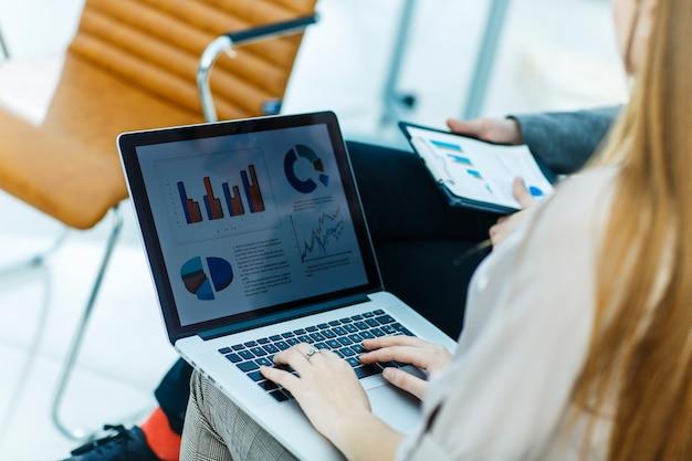 Equipo de negocios trabajando en una computadora portátil con horarios financieros en el lugar de trabajo.
