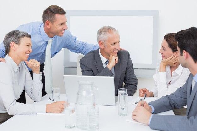 Equipo de negocios trabajando felizmente juntos en la computadora portátil