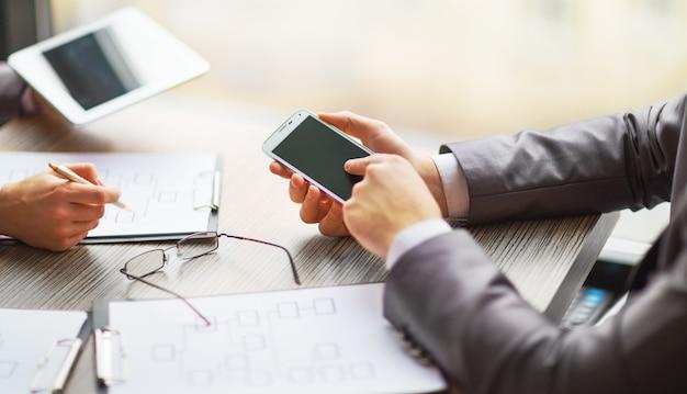 Equipo de negocios trabajando en un negocio de esquema utilizando la tableta y el teléfono inteligente