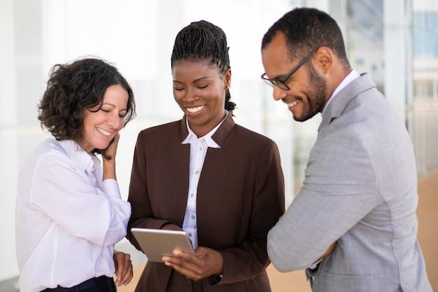 Equipo de negocios unidos feliz viendo video en tableta