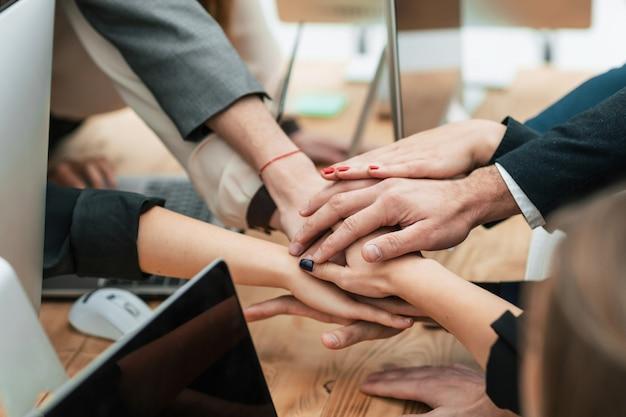 Equipo de negocios uniendo sus manos sobre el escritorio