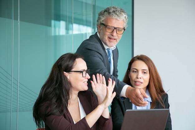 Equipo de negocios viendo y discutiendo la presentación en la computadora portátil, ejecutivo masculino apuntando a la pantalla