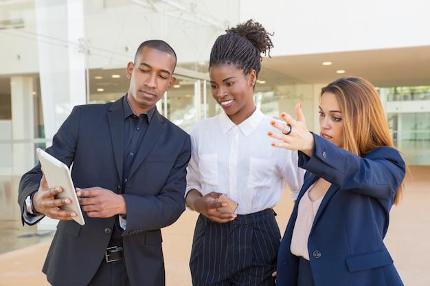 Equipo de negocios viendo la presentación del proyecto en tableta