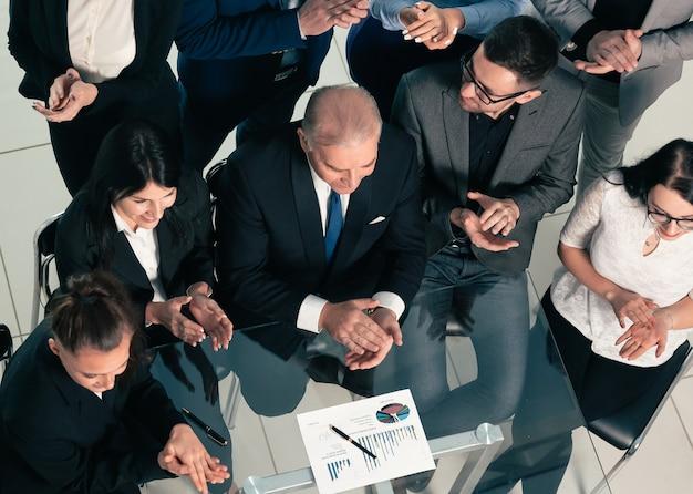 Equipo de negocios de vista superior aplaudiendo en el lugar de trabajo