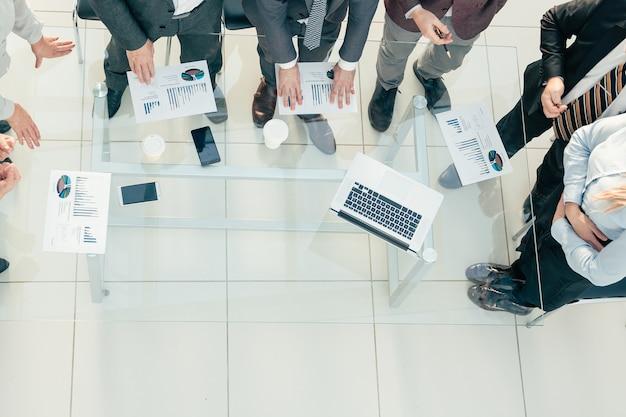 Equipo de negocios de vista superior discutiendo datos financieros en una reunión de oficina