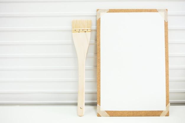 Equipo para tableros de dibujo, pinceles para obras de arte, colocado sobre una mesa blanca.