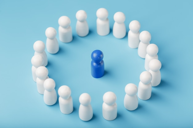 Un equipo de personas blancas se para y escucha al líder azul del líder. el concepto del líder del equipo de negocios.