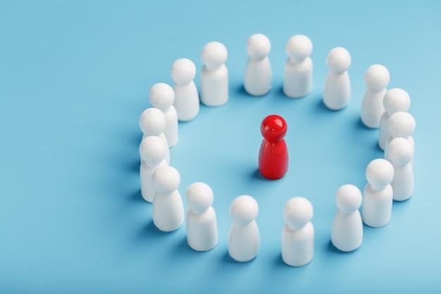 Un equipo de personas blancas se para y escucha al líder del líder rojo. el concepto del líder del equipo de negocios.