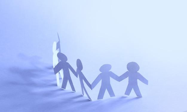 Equipo de personas de muñecas de papel cogidas de la mano