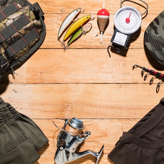 Equipo de pesca y ropa masculina sobre tabla de madera.