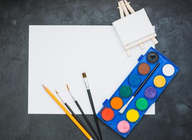Equipo de pintura y papel de dibujo blanco con caballete de madera en miniatura.