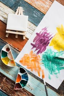 Equipo de pintura y papel pintado desordenado sobre fondo de madera.