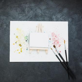 Equipo de pintura y papel de pintura manchada sobre superficie negra.