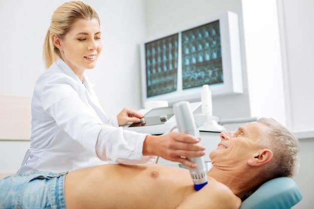 Equipo profesional. buen médico hábil profesional sosteniendo un dispositivo de ultrasonido y usándolo mientras verifica la salud de sus pacientes