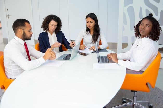 Equipo profesional de negocios con laptops y papeles.