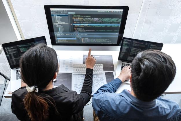 Equipo profesional de programador que trabaja en un proyecto en la computadora de desarrollo de software en la oficina de la empresa de ti, escribiendo códigos y sitios web de códigos de datos y tecnologías de base de datos de codificación en una nueva aplicación.