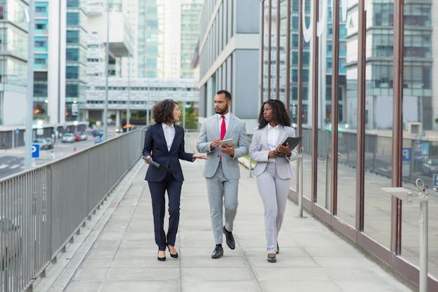 Equipo de profesionales de negocios hablando en la calle
