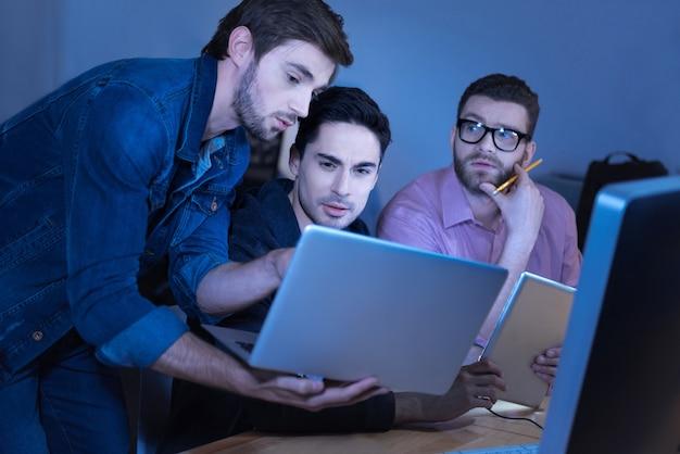 Equipo de programadores. atractivo hombre inteligente brutal sosteniendo una computadora portátil y mostrando algo a sus colegas mientras trabaja en equipo
