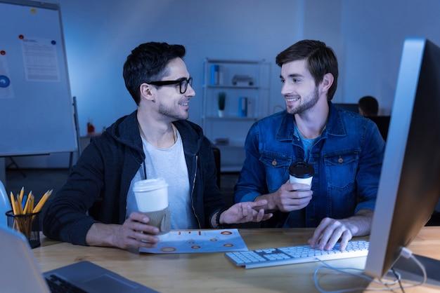 Equipo de programadores. hombres positivos alegres encantados tomando café e interactuando entre sí mientras disfrutan de su trabajo