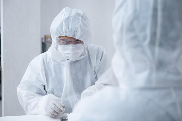 Equipo de químicos en traje de protección médica inventando e investigando un medicamento antiviral