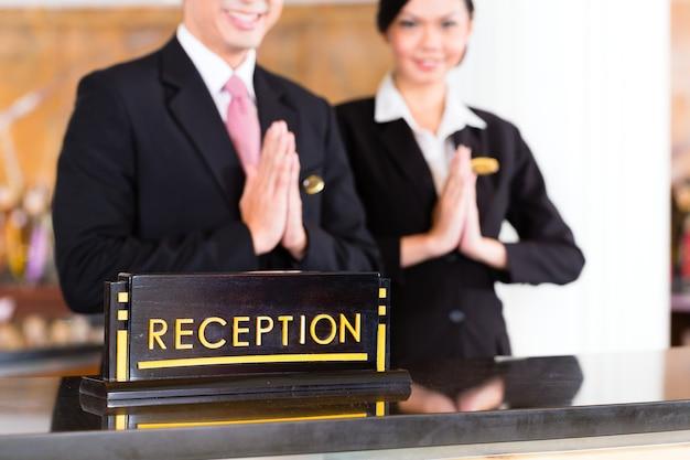 El equipo de recepción chino asiático en la recepción del hotel de lujo da la bienvenida a los huéspedes con un gesto típico, una señal de buen servicio y hospitalidad